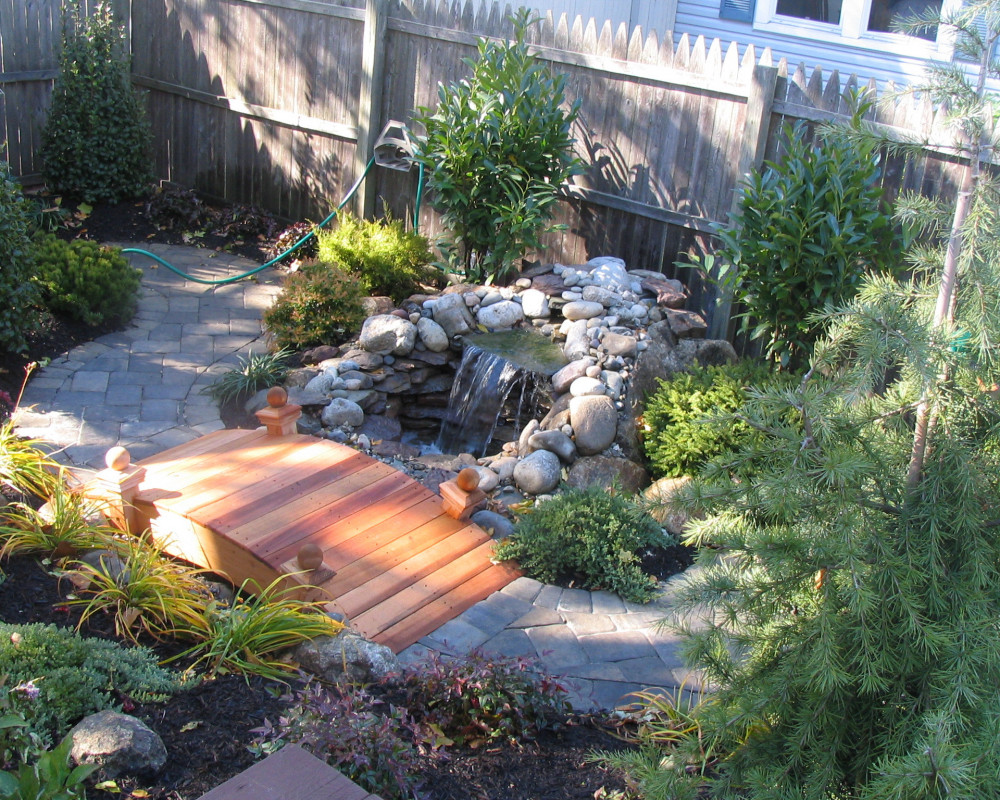 Small backyard redo with a water feature and bridge.