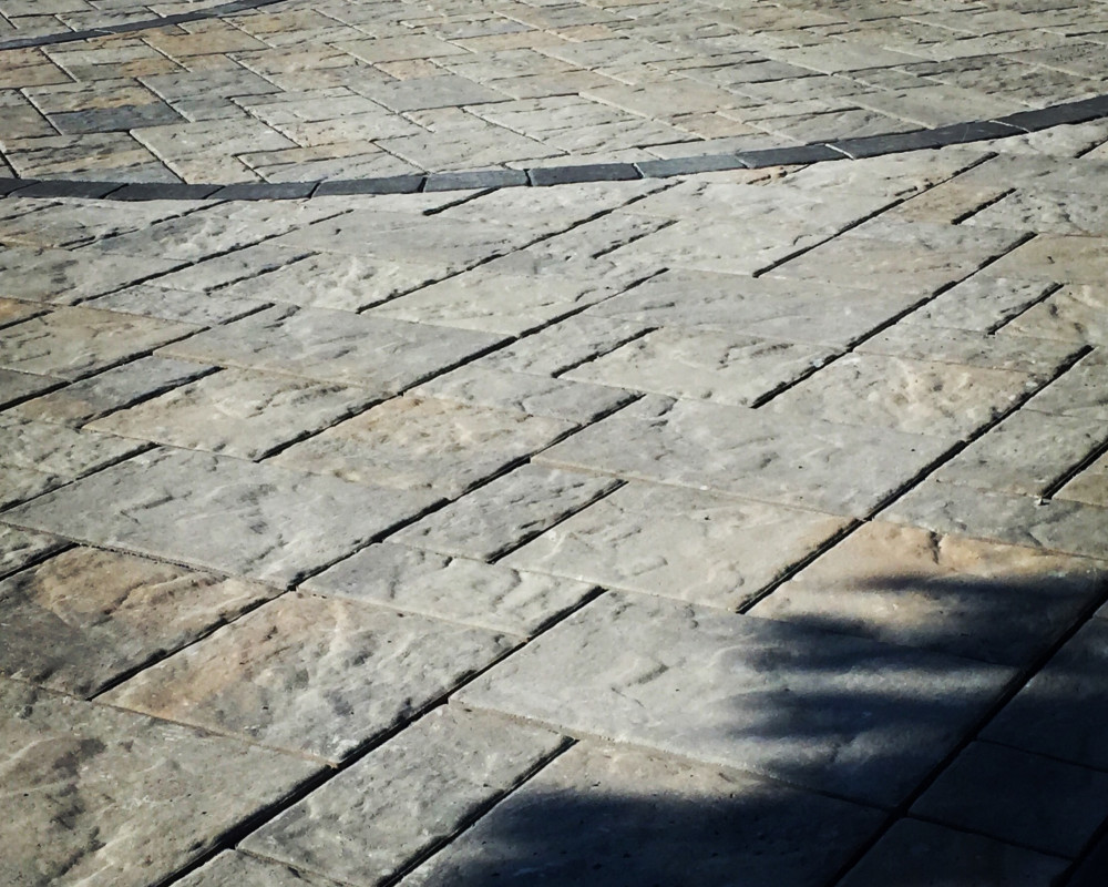 Blu 80 Pavers in Champlain Grey with concentric circle details and 45° in-lay, Parisien framing in onyx.