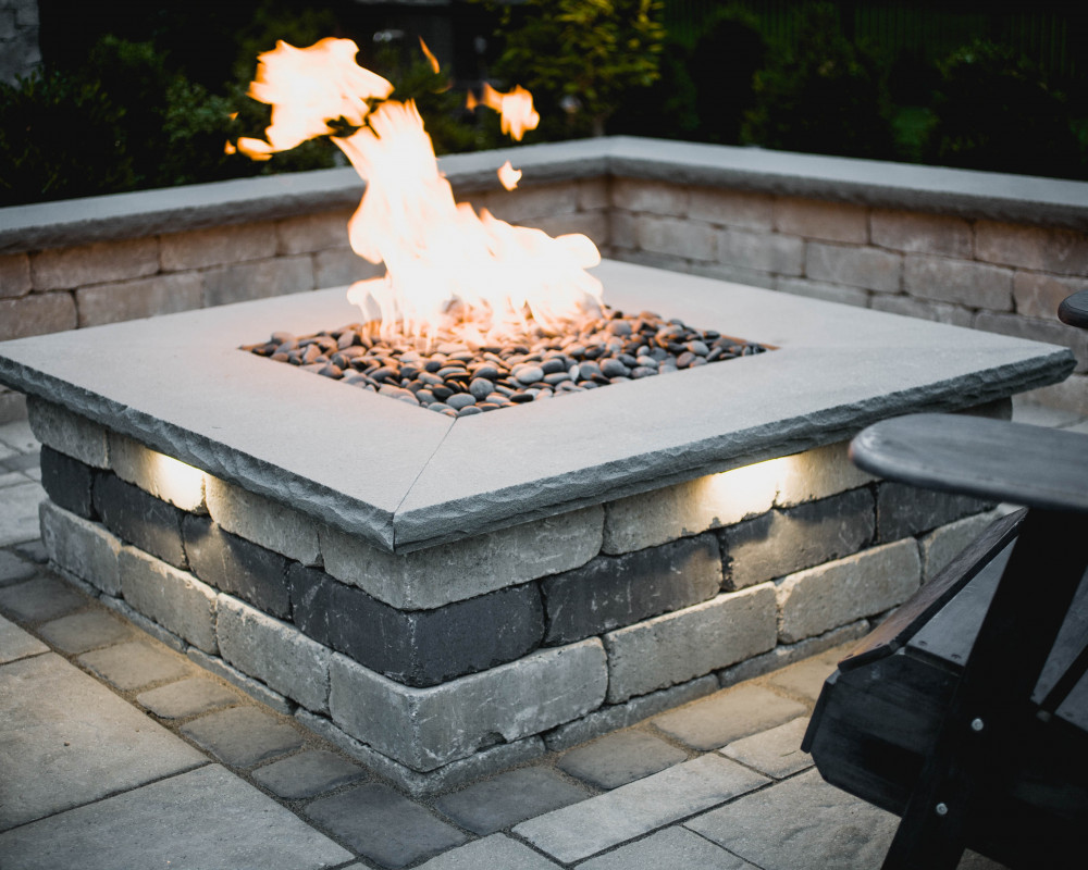 Custom square fire pit with (4) LED hardscape lights to add interest and extend this space into the the dark hours of the night. Techo-Bloc Manchester wall offers a timeless tumbled look and feel.