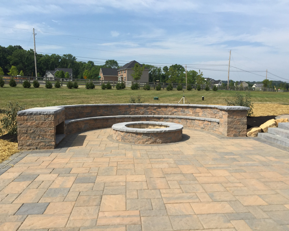 This custom fire pit and bench was built with Techo Bloc's Mini Creta wall block and portofino caps.  The space is capped off with a wood storage bin and lighting in the bench.