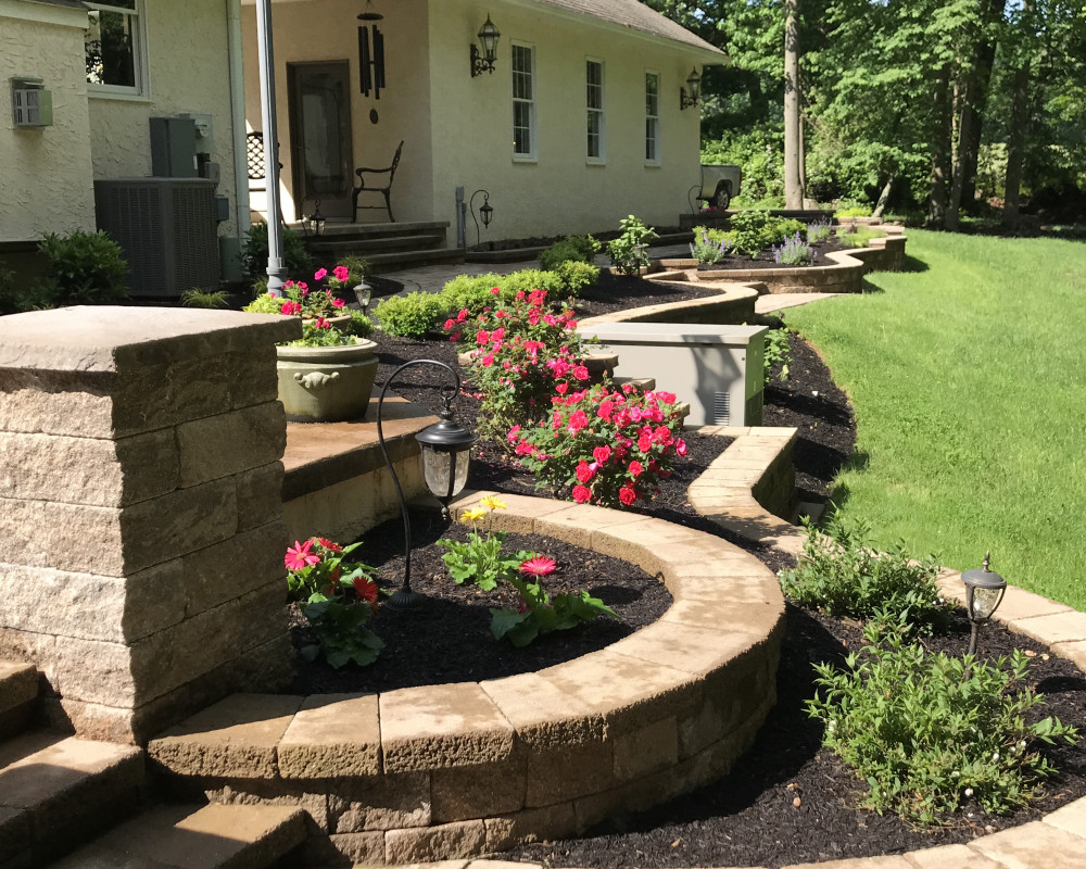 This slope behind the house in Pottstown, PA was terraced into colorful gardens using Mini Creta wall block and Blu 60 walks with a diverse plant list to add color and interest year around.
