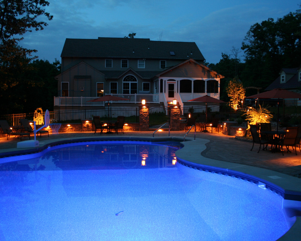This poolside patio is one of our favorite projects!  Special touches include tiered wall & pillar caps, permeable paver borders, stormwater retention and infiltration under the patio, and all LED lighting.