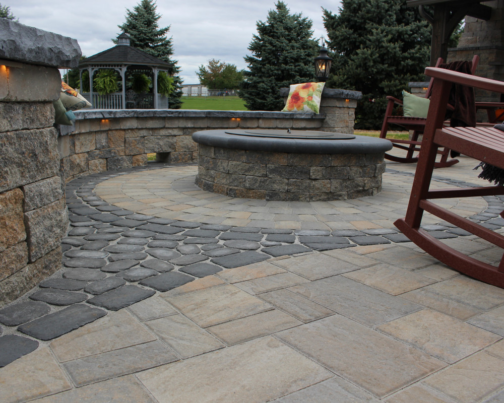 A Valencia fire pit is accented with Antika, Parisien, and Villagio pavers.  A Zentro smokeless insert was installed in the fire pit.  The seating wall & pillars feature a tiered cap.