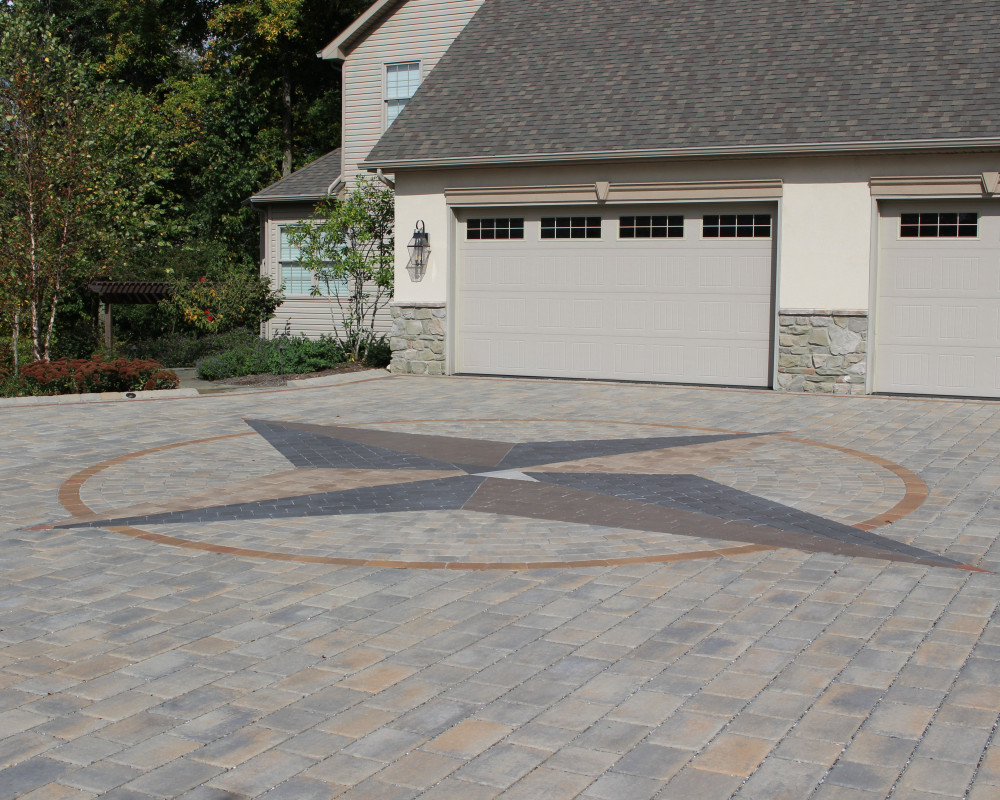 The centerpiece of this large permeable paver driveway is the 30' custom compass rose.  The failing, clogged permeable asphalt driveway was entirely removed.  The driveway was sealed to reduce movement of the permeable joint fill.  The driveway was enlarged to create additional parking.