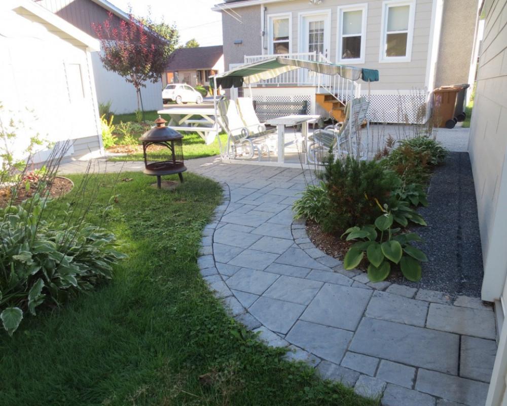 La propriétaire de cette résidence désirait rénover son vieux patio de dalle de béton par une surface de pavage de béton, mais qui réunirait la porte du garage et de la remise de façon harmonieuse et esthétique.