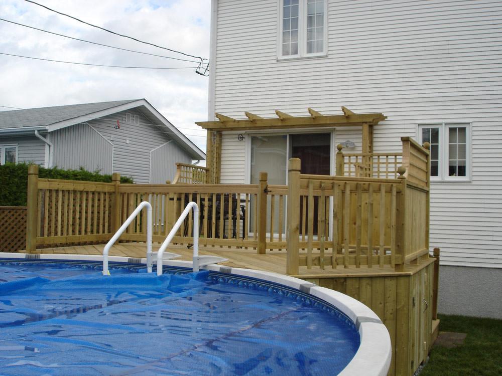 Le client de ce projet désirait relier le patio existant à la piscine hors terre, sans pour autant compromettre l'aspect esthétique du projet. Nous avons dons proposé à nos clients un patio à un niveau, mais séparé d'un  garde de sécurité, pour permettre aux jeunes enfants d'avoir accès à la piscine en toute sécurité. Les courbes et la tonnelle au-dessus de la porte-fenêtre confèrent à projet un cachet unique et très harmonieux.