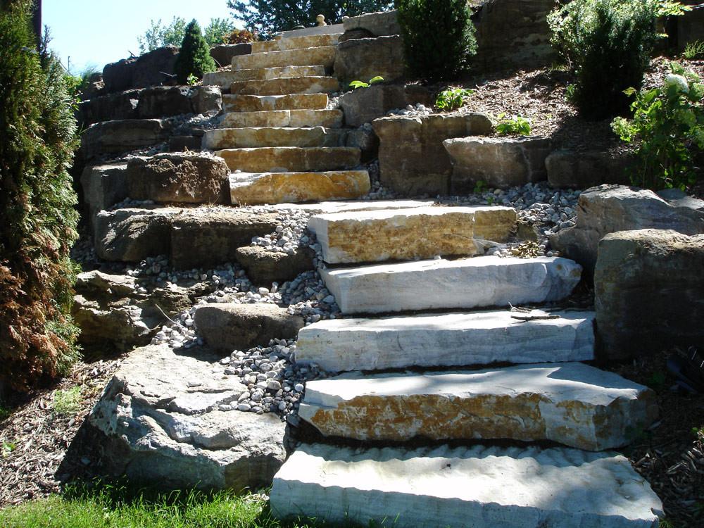 Ces escaliers font parties d'un ensemble d'éléments d'un vaste projet d'aménagement résidentiel. La hauteur et la forte pente sur ce site rendaient la circulation très difficile. Le client voulait pouvoir descendre et monter en toute sécurité, afin d'avoir un accès à la rivière. Plusieurs possibilités étaient sur la table, mais nous avons privilégié une approche plus naturelle et proposé aux clients de belles grosses marches de pierres naturelles qui s'harmonisaient très bien avec la résidence et l'environnement existant.
