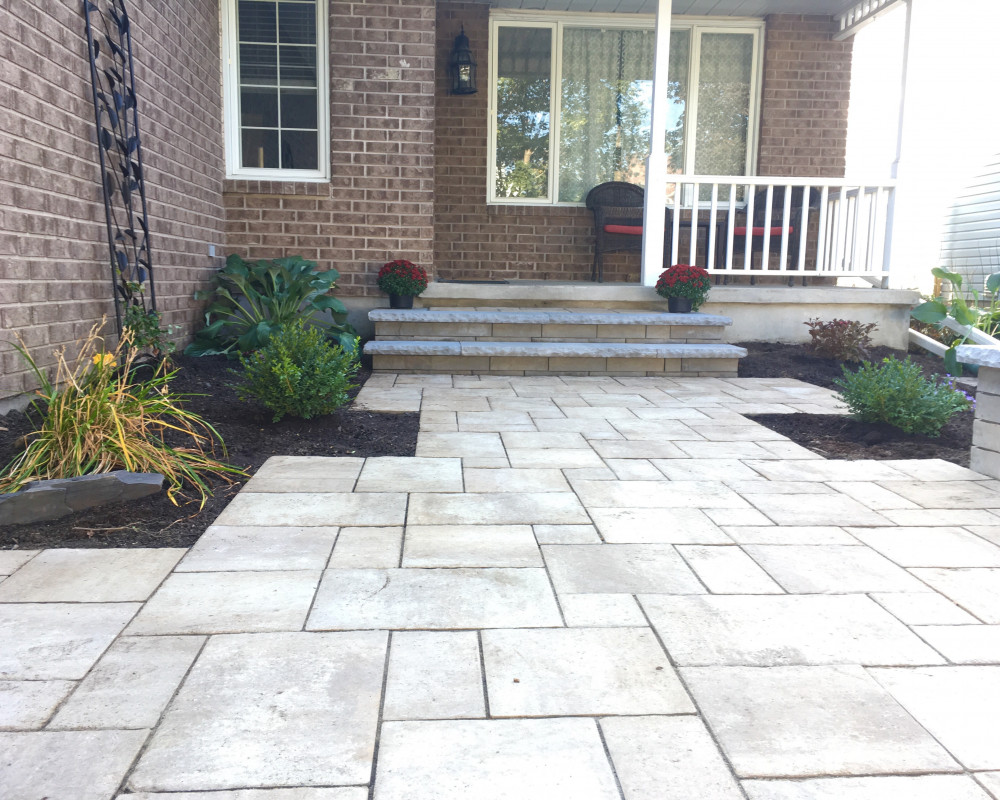 Beautiful modern front entrance in the Orleans area. This project highlighted the Techo Bloc  BLU 60mm Slate stone. Utilizing Techo Bloc's Brandon Wall 90mm for the front main steps and side sitting bench, we decided the delicate touch of the York Cap added to the natural feel the client desired.