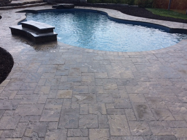 A backyard paradise for sure. We designed this property to be the place you want to be. The ample patio outdoor living area is covered with Techo Bloc BLU 60mm Slate and precise  cut Techo Bloc Bullnose pool coping. With a custom scribe outside edge for a wider visual feel to the swimming pool surround, along with defined edges for a dramatic feel with black mulch.
