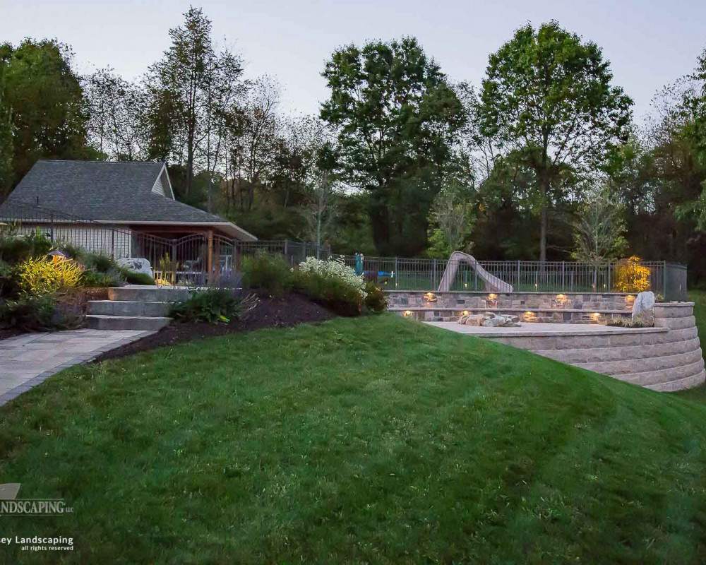 A great example of how a large retaining wall comprised of Techo-Bloc Suprema wall block can give one the capability to transform a backyard into a functional outdoor living space.