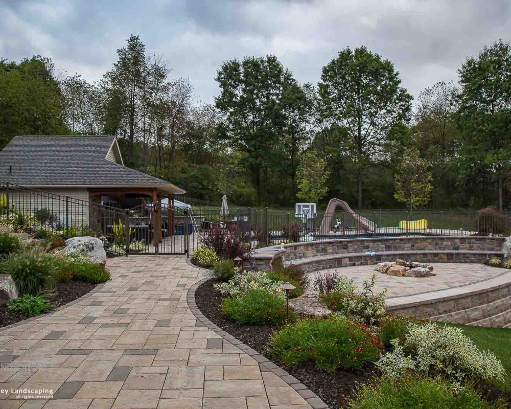 A beautiful collection of Techo-Bloc products comprised of Blu 60 slate pavers with a Villagio border, a large Mini-Creta Architectural seating wall, and a Suprema retaining wall