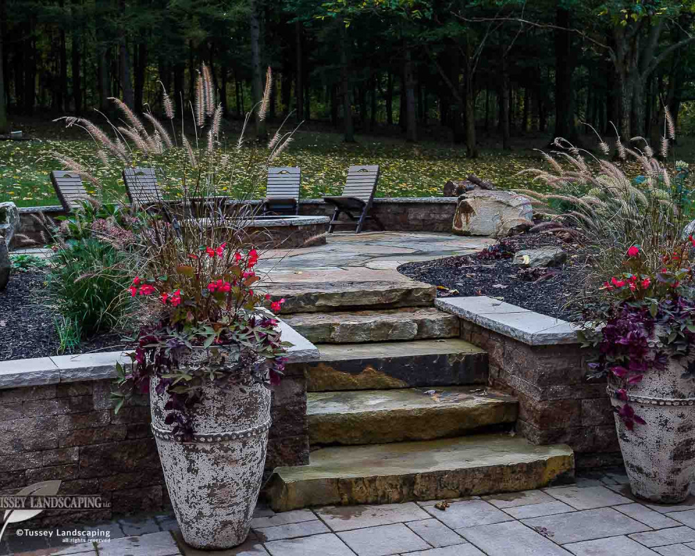 A nice collection of mini-creta architectural retaining walls with a york cap, blu 60 slate pavers, Black Hills natural stone slab steps, as well as Black Hills natural flagstone patio.