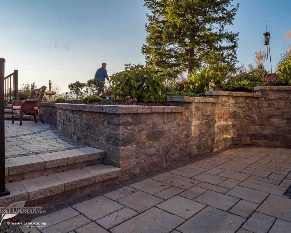 Outdoor living spaces comprised of mini-creta Architectural retaining wall with an Architectural cap, Blu 60 slate pavers and a Villagio paver border.