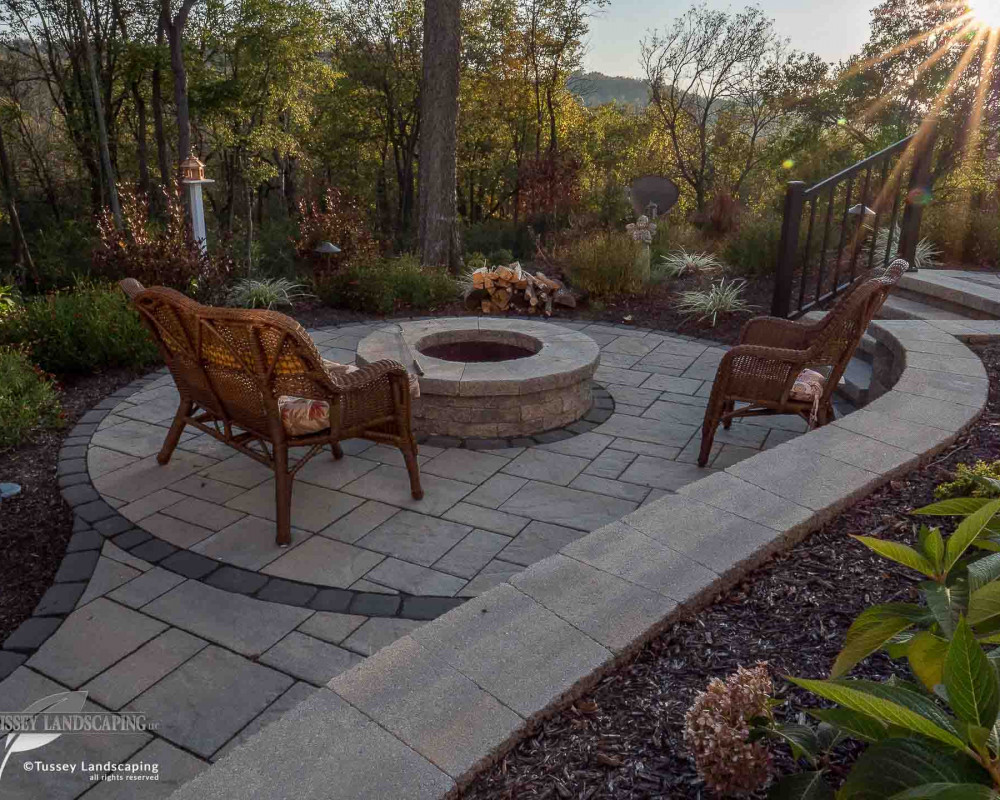 A beautiful secluded fire pit area featuring Techo-Bloc Sandlewood Blu 60 mm slate pavers with a Villagio border. A mini-creta architectural fire pit and retaining wall with an Architectural cap