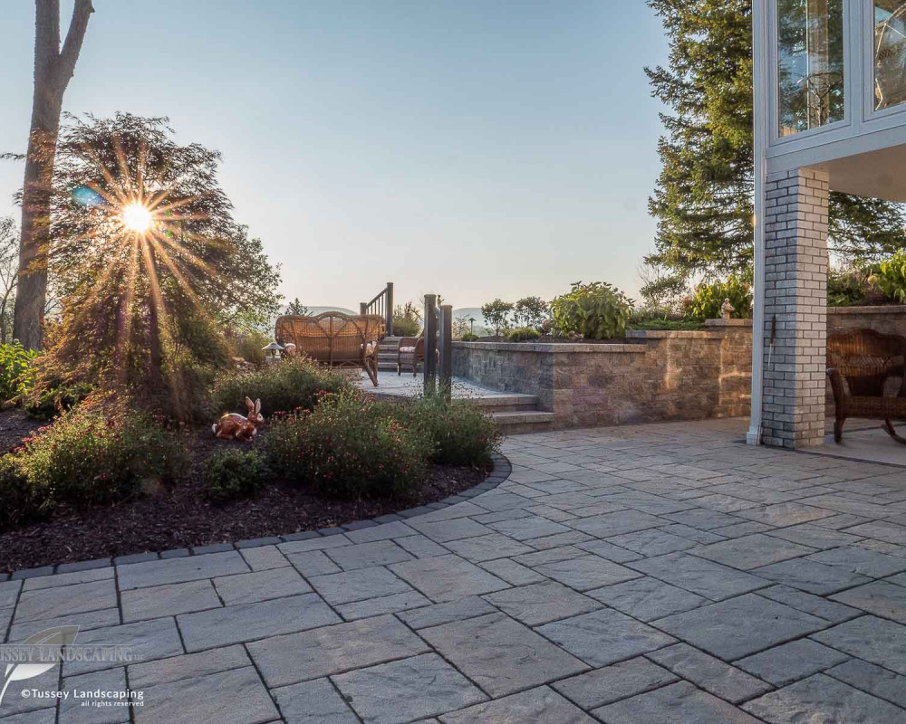 This paver patio features Techo-Bloc Blu 60 mm slate pavers with a Villagio paver border. In the background you can view a mini-creta retaining wall.