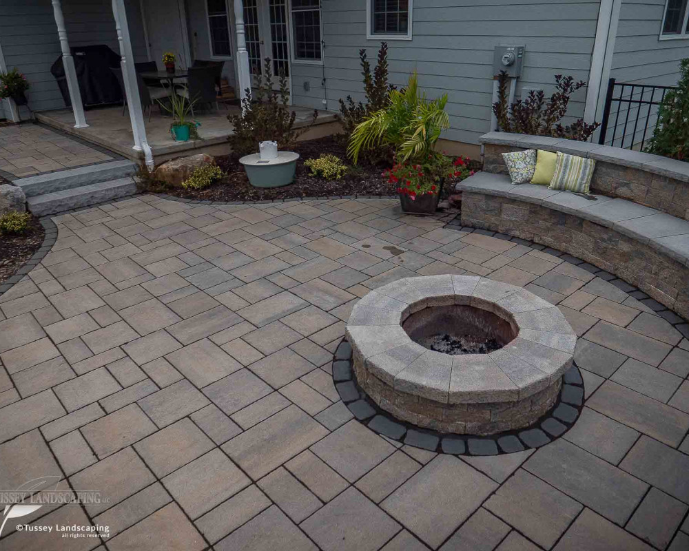 This outdoor room is comprised of Techo-Bloc's Blu 60 mm slate pavers with a Villagio border, a Mini-Creta fire pit and seating wall, as well as York slab steps.