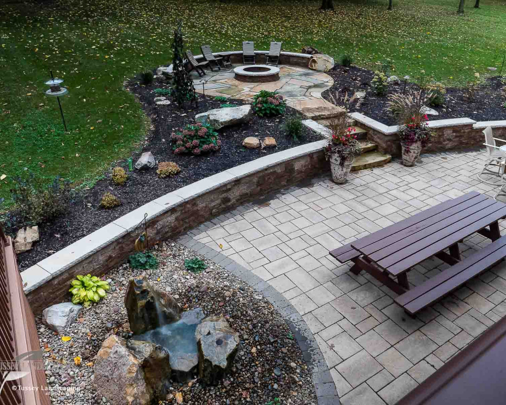 "Outdoor Living Space including Techo-Bloc Blu 60 mm Slate pavers with a soldier course of the Hera 6"" x 9"" pavers. Also featured is a mini-creta Architectural retaining wall with a York Cap."