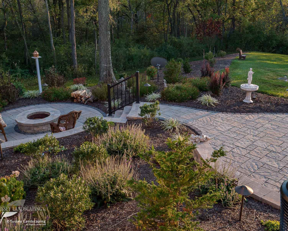 Outdoor living space comprised of Techo-Bloc's Blu 60 mm textured slate pavers with a Villagio border. Rocka slab steps, and Mini-Creta fire pit and retaining walls.