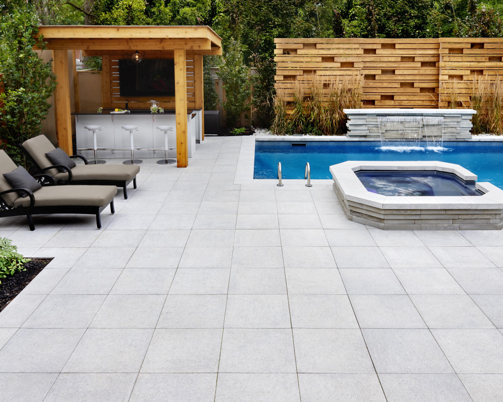 This is a one of a kind design, with Polished Greyed Nickel Industria slabs and a custom bar and privacy fencing designed to match the graphic wall spa and waterfall. Clean lines and Modern design.