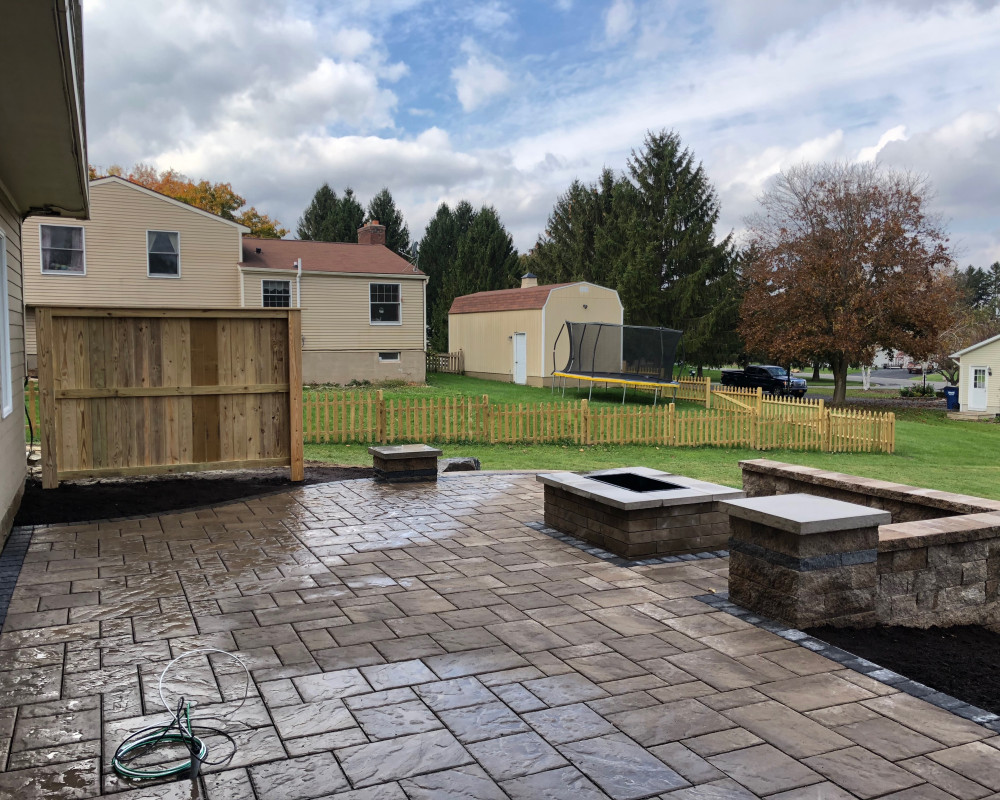 New patio using Blu60 slabs provide sitting space and platform for a new hot tub. Mini-creta walls with pillar accents provide dimension and gathering spot around the Brandon Rectangular Fire pit.