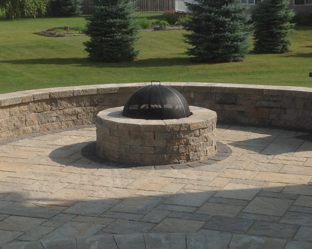 Bi-level patio offering gathering space around the Valencia Fire Pit. Sitting wall crafted from Mini-Creta wall blocks provide extra sitting room and dimension in the space. Accent around fire pit and edges of patio with Hera paver in charcoal.