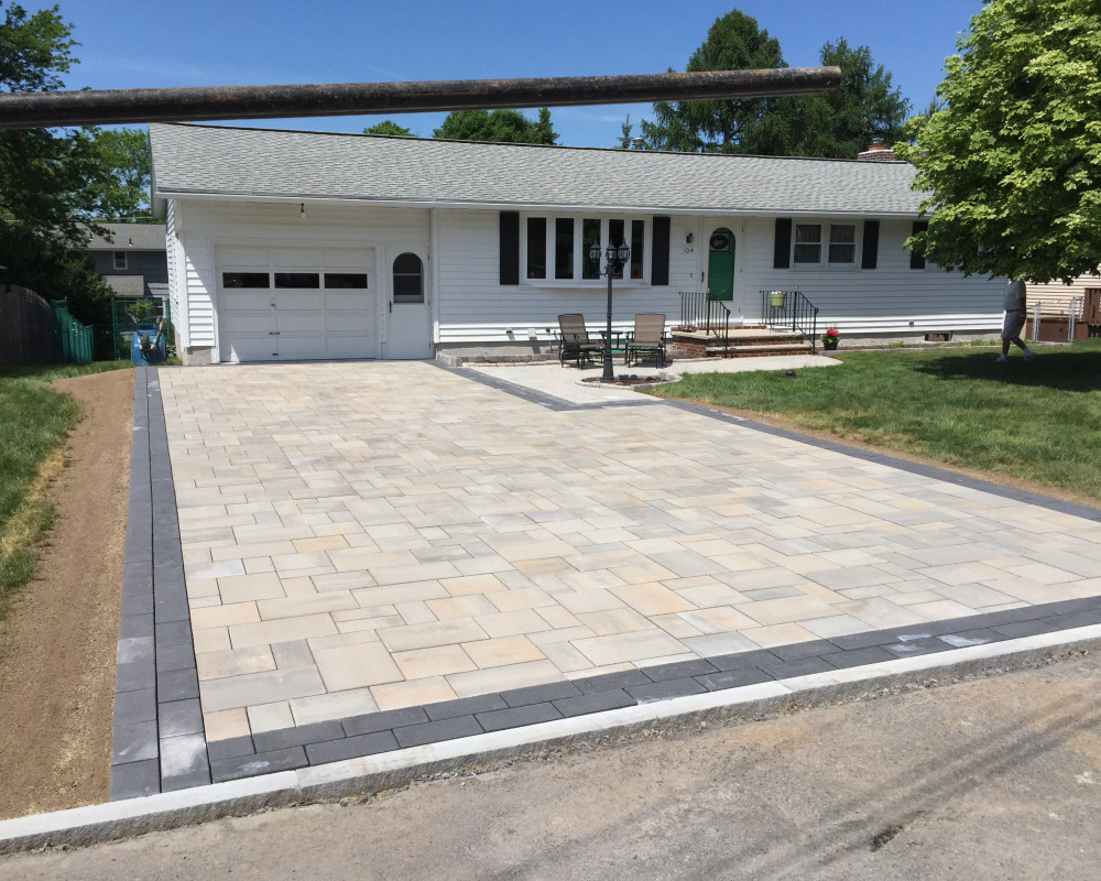 "Blu80 Slabs were used to create this stunning driveway.  Border with 6"" by 13"" slabs for accent. Granite curbing contains the pavers at street side."