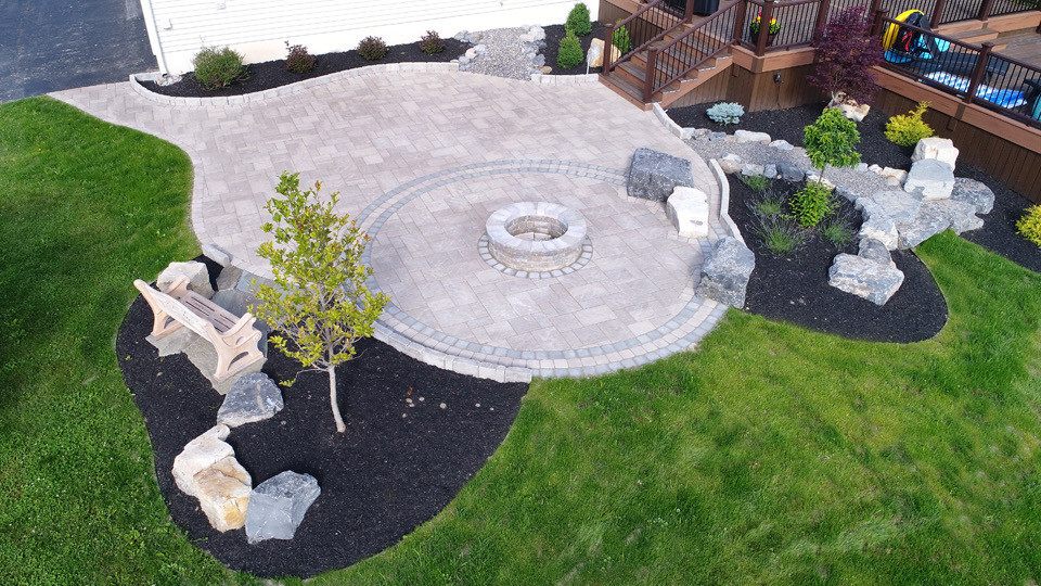 Backyard makeover including an expansive patio offering fire pit area and sitting rocks. Connection to raised composite deck and pool space.