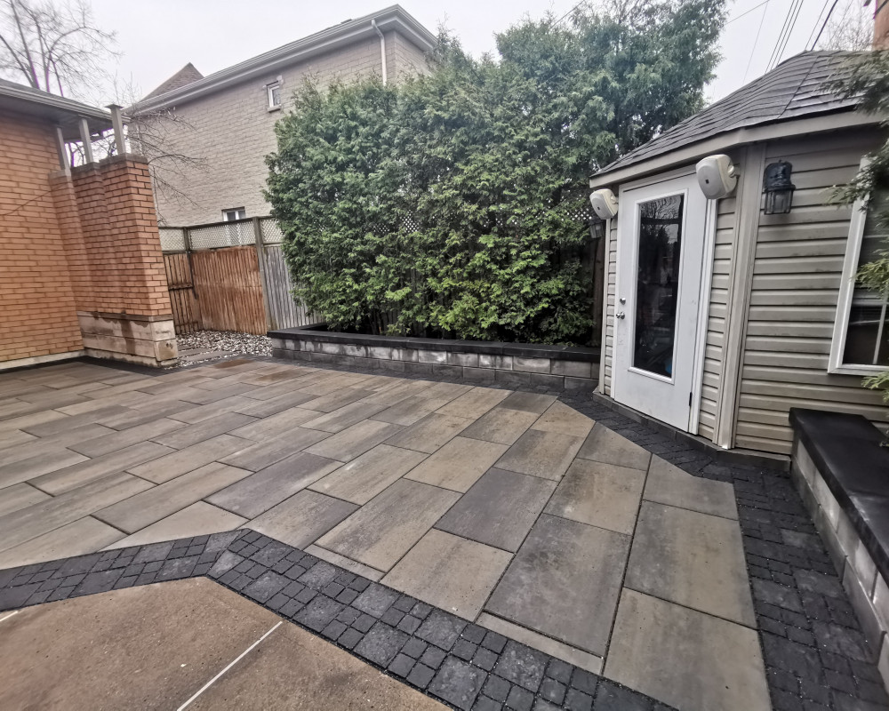 This patio was installed in a permable manner to allow this smaller yard drain properly.  The walls are used as benches and have lighting every 3 feet.
