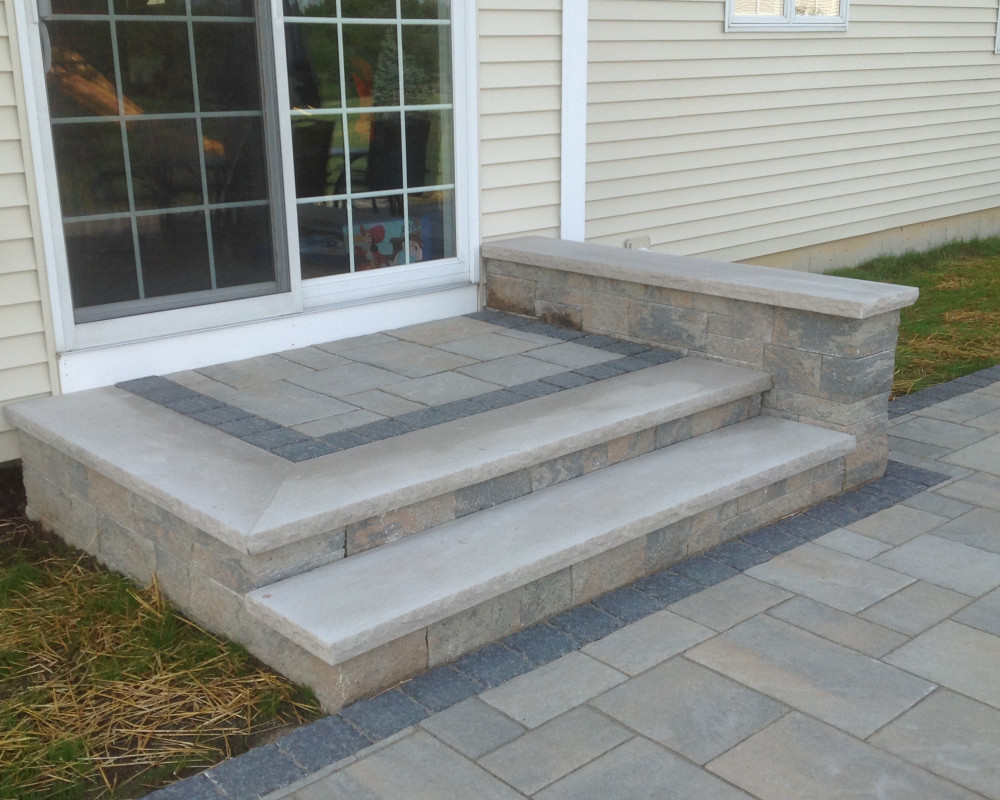 Custom landing with short seat wall provides a transition from house to patio. Mini-Creta landing and risers, with Blu60 slab interior & accent banding in charcoal.