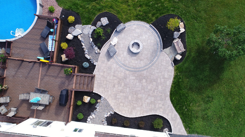 Direct view from above of this unique organic patio and adjacent composite deck/pool. Natural boulders rise out of the patio, offer sitting space around the fire pit.